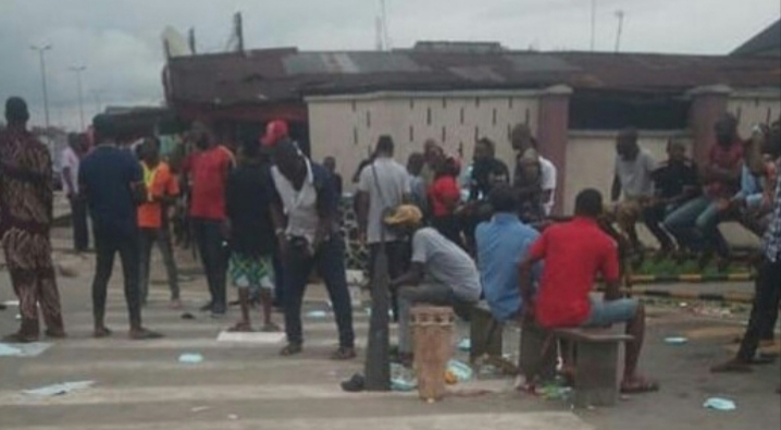 Youths cook with firewood in front of Shell company as they protest sacking of their kinsmen in Rivers