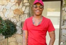 Somizi signs copies of his cookbook for a lady and her employees
